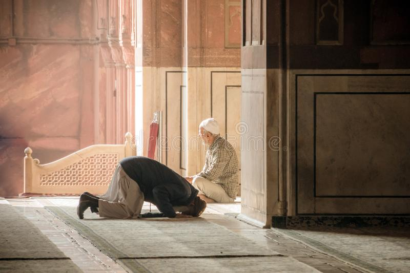 Religious muslim man praying inside the mosque. Two older Muslims at the great Friday Mosque Jami Masjid in New Delhi, India. 8 Ja stock photography