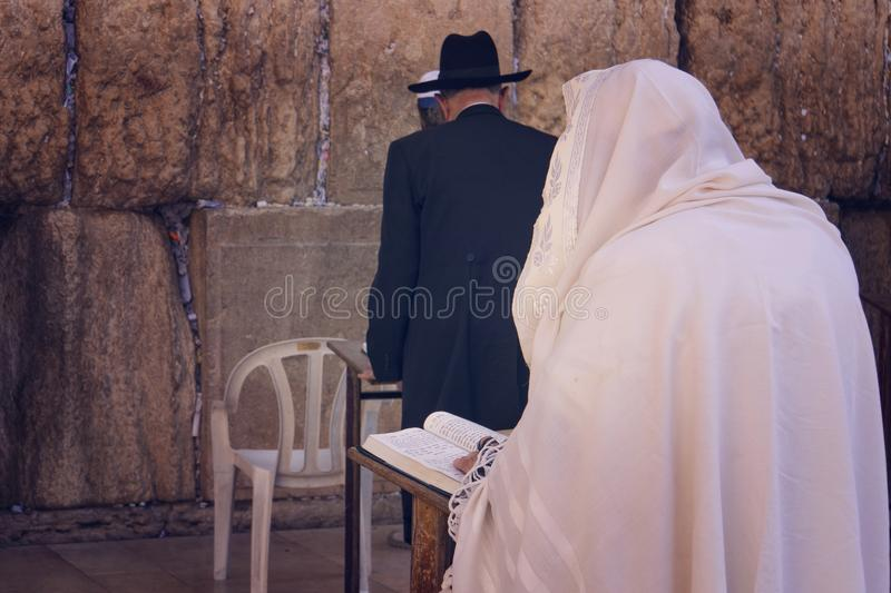 Religious orthodox Jew in the foreground wearing a prayer shawl draped prays at the Western wall, Jerusalem, Israel. Male figure royalty free stock photo