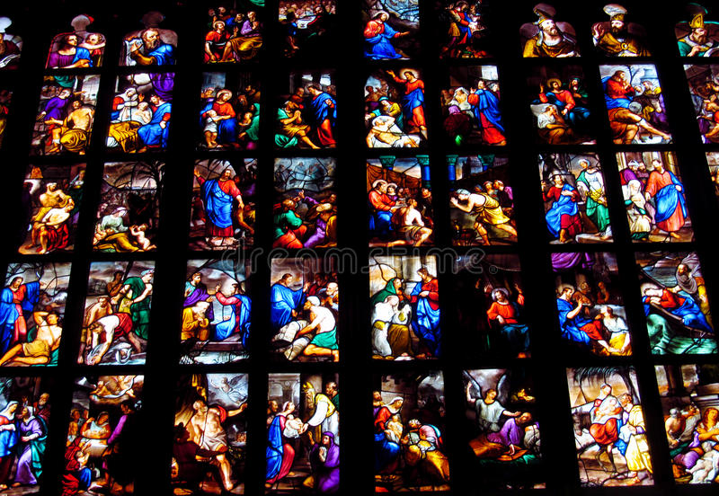 Religious picture on stained glass in the church stock images