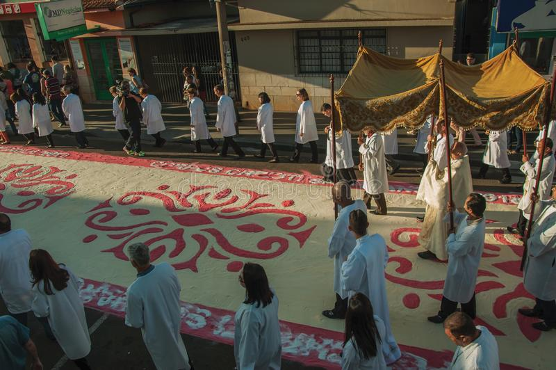 Religious procession on colorful sand carpet at the Holy Week. Sao Manuel, Brazil - May 31, 2018. Religious procession passing by a colorful sand carpet at the stock image