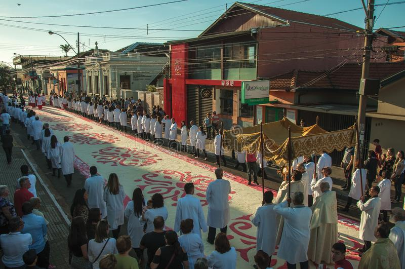 Religious procession on colorful sand carpet at the Holy Week. Sao Manuel, Brazil - May 31, 2018. Religious procession passing by a colorful sand carpet at the stock photography