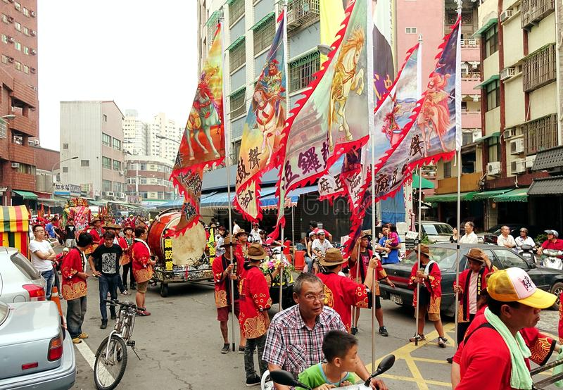 Religious Procession with Flags and Drums. KAOHSIUNG, TAIWAN -- APRIL 20, 2014: A religious procession with flags and drums makes its way through a narrow street stock image