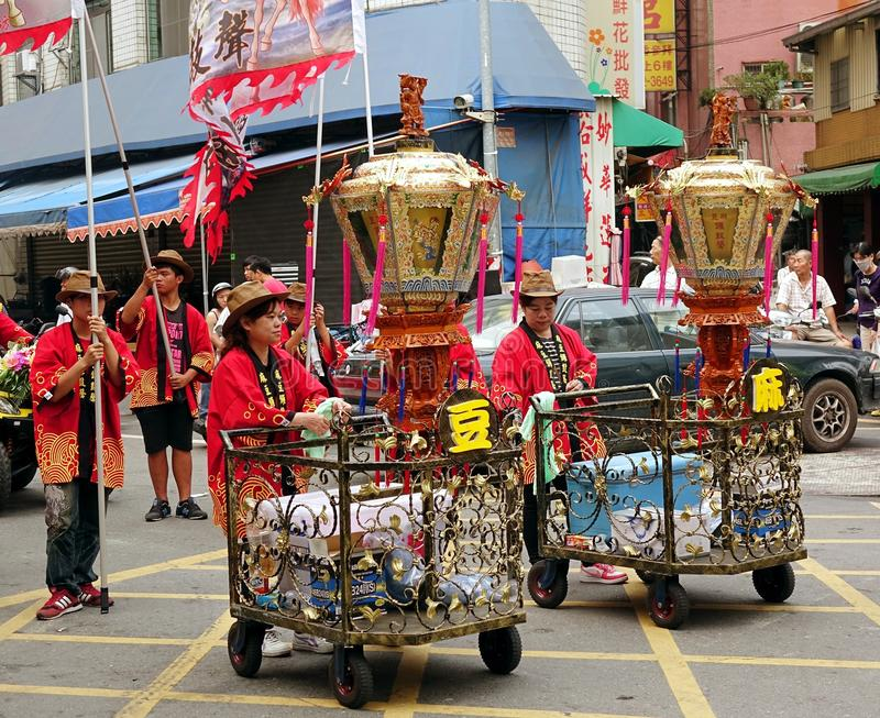 Religious Procession in Taiwan. KAOHSIUNG, TAIWAN -- APRIL 20, 2014: Unidentified women push carts with ceremonial lanterns at a local religious procession royalty free stock photography