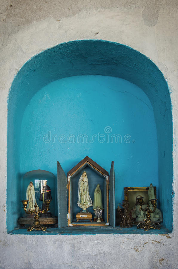Religious Shrine. Blue shrine carved on a white wall with religious figures of virgin Mary stock image