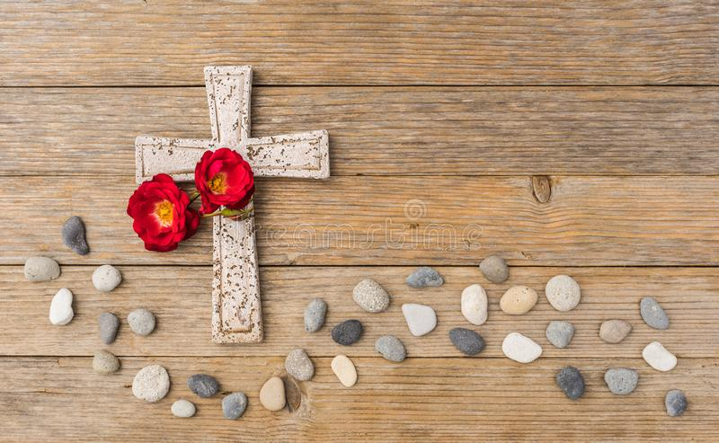 Stone cross with roses and wave of pebbles on wood background for grief and death concept stock photo