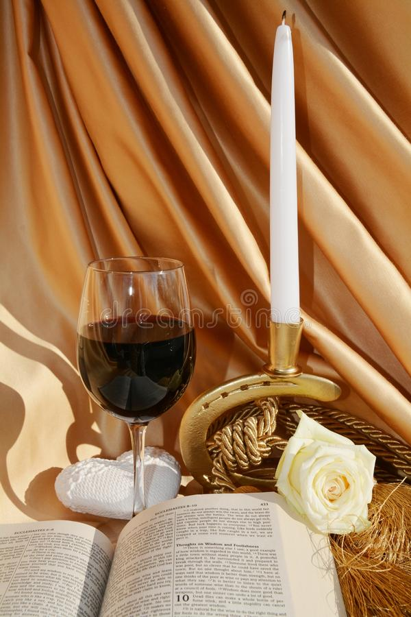 Religious symbols. The Bible, a candle, a rose, a glass of red wine and a heart, on a golden beautiful background, as religious symbols stock images