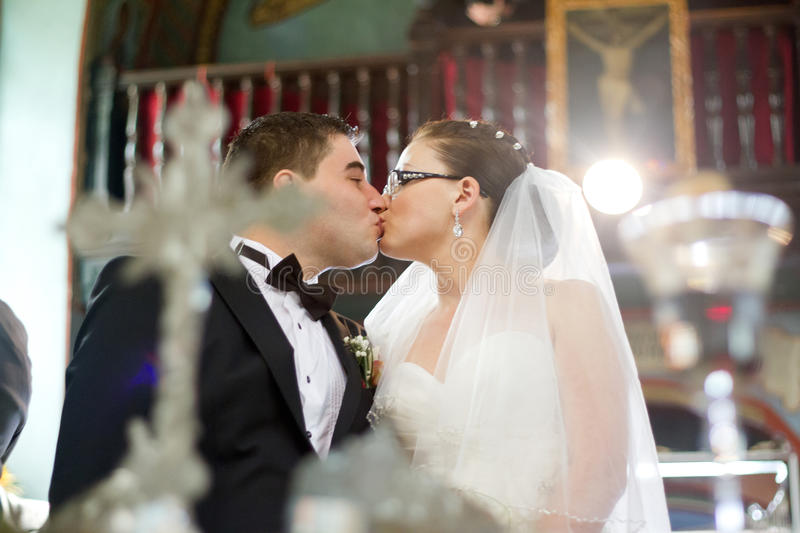 Religious wedding ceremony. Bride and groom kiss at religious wedding ceremony in church stock images