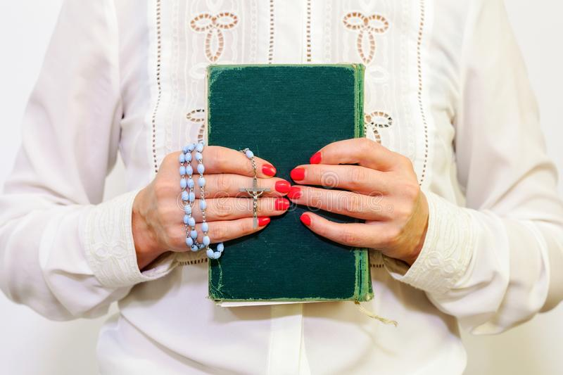 Religious woman holding Holy Bible and rosary. Close up stock photo