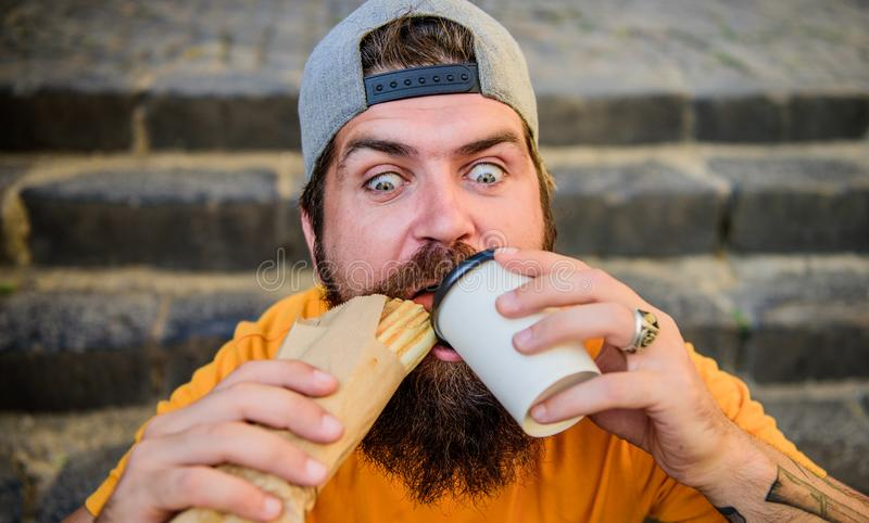 Relish the moment. Hipster drinking coffee with hotdog snack on stairs outdoor. Bearded man dining with unhealthy. Sandwich and beverage snack. Hungry guy stock photography