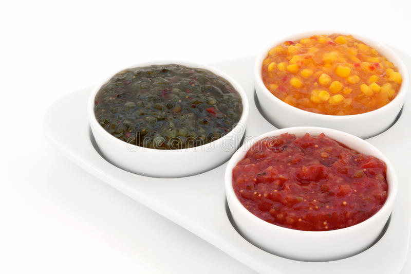 Relish Selection. Burger relish selection of red tomato, green gherkin and sweetcorn in a triangular porcelain dish with bowls, isolated over white background stock photo