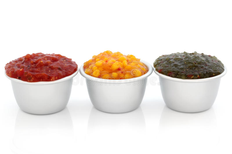 Relish Selection. Burger relish selection of tomato, sweetcorn and gherkin in metal serving dishes, over white background stock photography