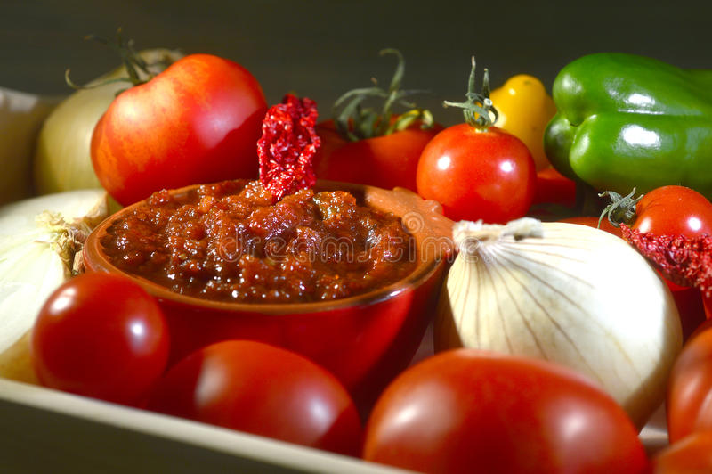 Relish tomato. Relish tomatoes with peppers onions and spices in a bowl on a tray stock photos