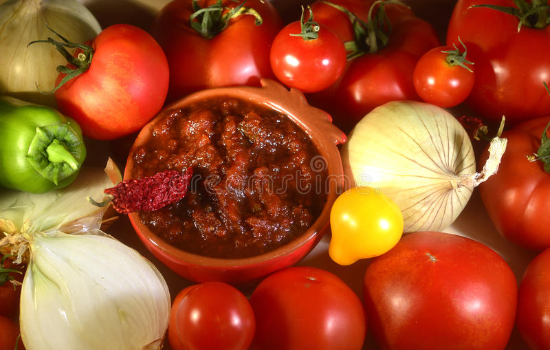 Relish tomato. Relish tomatoes with peppers onions and spices in a bowl on a tray royalty free stock photography