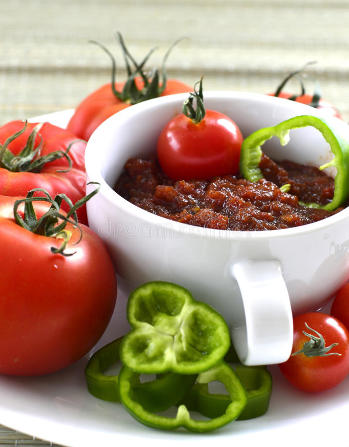 Relish tomato. Relish tomatoes with peppers onions and spices in a bowl on a tray royalty free stock photos
