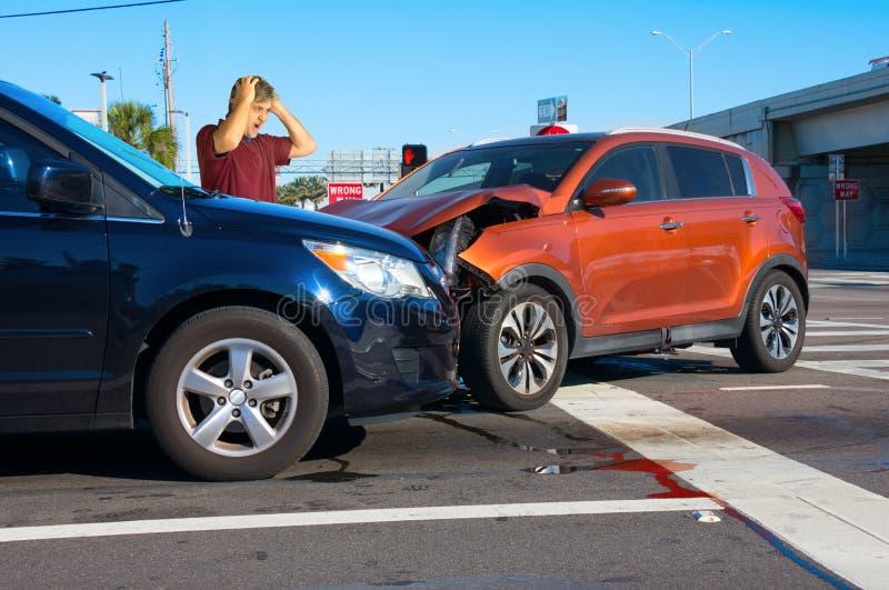 Relitto serio dell'automobile all'intersezione con l'autista molto turbato dell'uomo che esamina danno fotografia stock libera da diritti