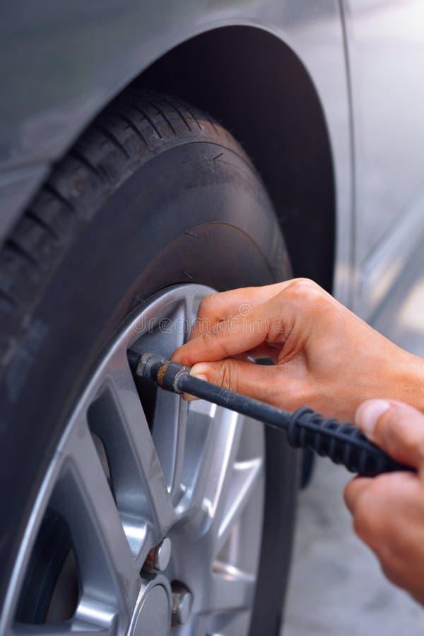 Rellenar el aire en el neumático de coche fotos de archivo