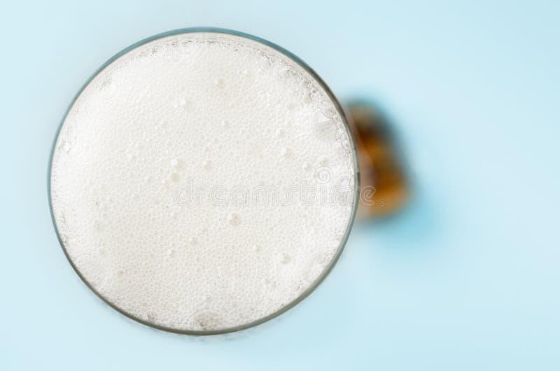 Relleno Champagne Glass de las burbujas con el corcho desde arriba en azul foto de archivo