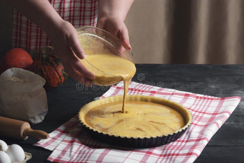 Relleno de colada del pastel de calabaza de la mujer de un cuenco en una bandeja, en una tabla rústica negra, rodeada por los ing foto de archivo