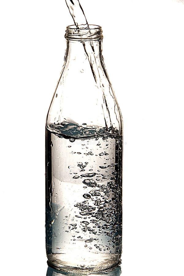 Relleno de una botella por el agua imagen de archivo