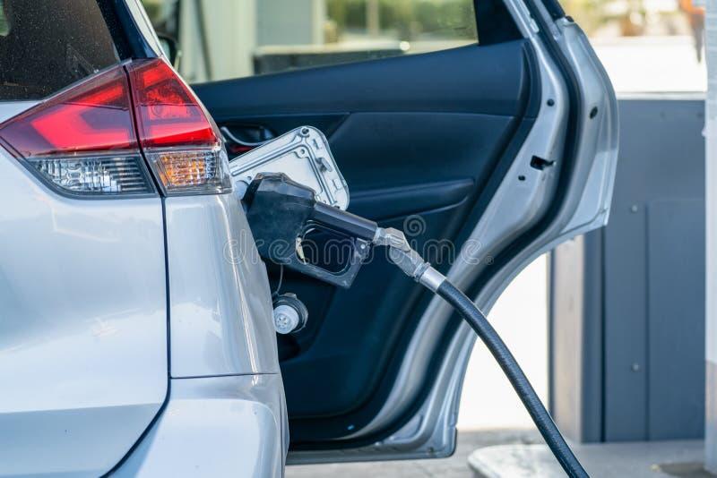 Relleno del coche encima del depósito de gasolina en una gasolinera, con la puerta abierta ilustración del vector