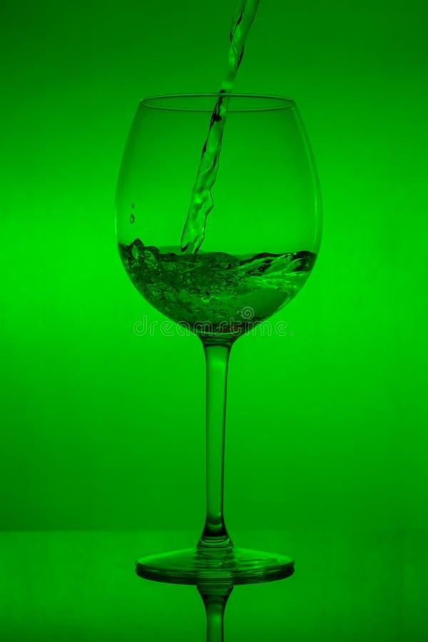 Relleno del vidrio, copa de colada en fondo verde fotos de archivo