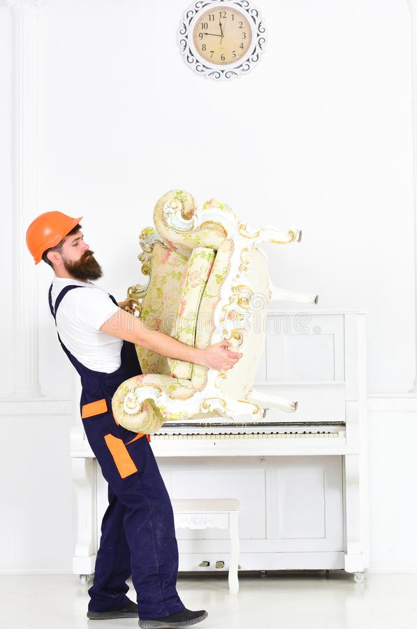 Relocating concept. Courier delivers furniture in case of move out, relocation. Loader carries armchair. Man with beard. Worker in overalls and helmet lifts up royalty free stock photos