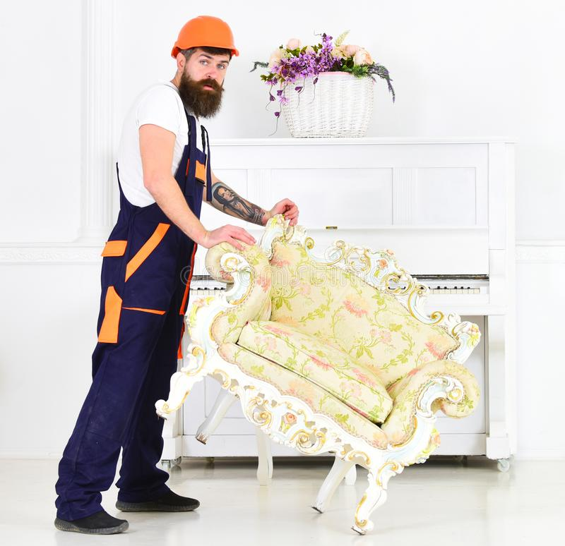 Relocating concept. Courier delivers furniture in case of move out, relocation. Man with beard, worker in overalls and royalty free stock images