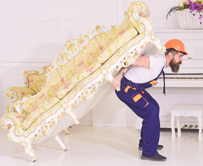Relocation concept. Courier delivers furniture in case of move out, relocation. Loader moves sofa, couch. Man with beard. Worker in overalls and helmet carries royalty free stock photos