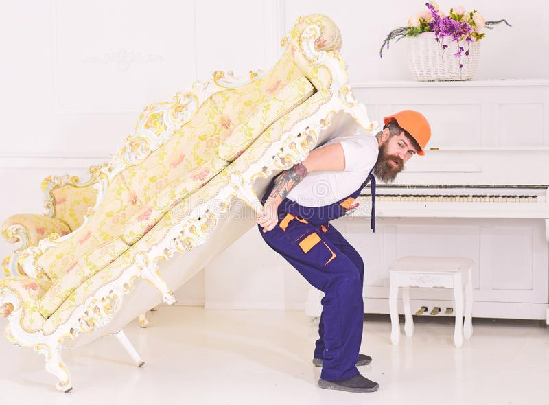 Relocation concept. Loader moves sofa, couch. Man with beard, worker in overalls and helmet carries sofa on back, white. Background. Courier delivers furniture royalty free stock photography
