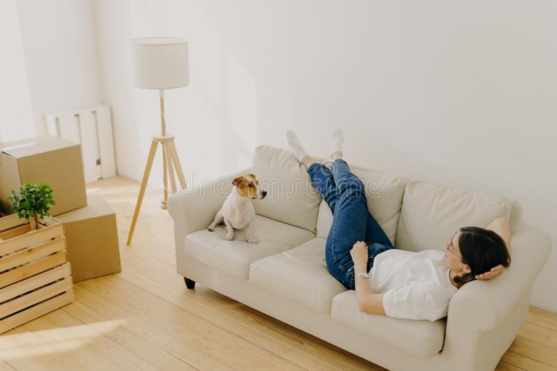Relocation and mortgage concept. Relaxed brunette woman has rest on comfortable sofa, wears t shirt, jeans and white socks, plays stock photos