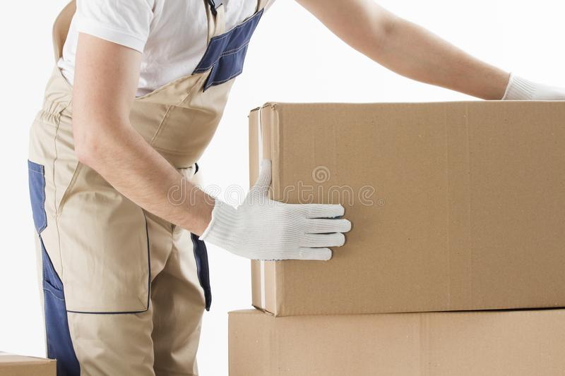 Relocation services concept. Mover in uniform with cardboardboxes isolated on white background royalty free stock photo
