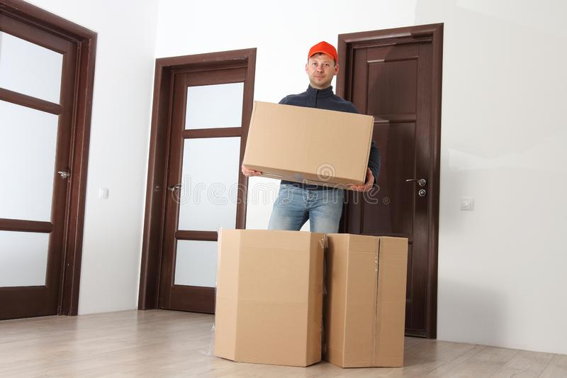 Relocation worker with cardboard boxes in apartment stock image