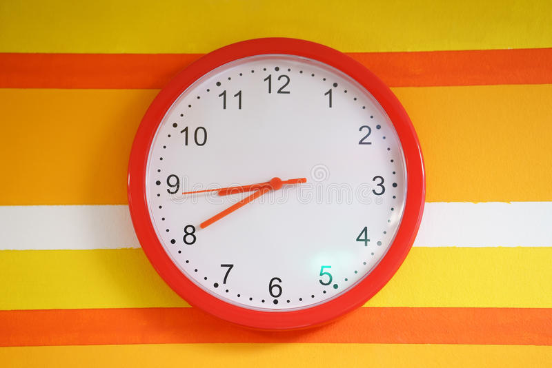 Reloj anaranjado de la pared en colorido foto de archivo