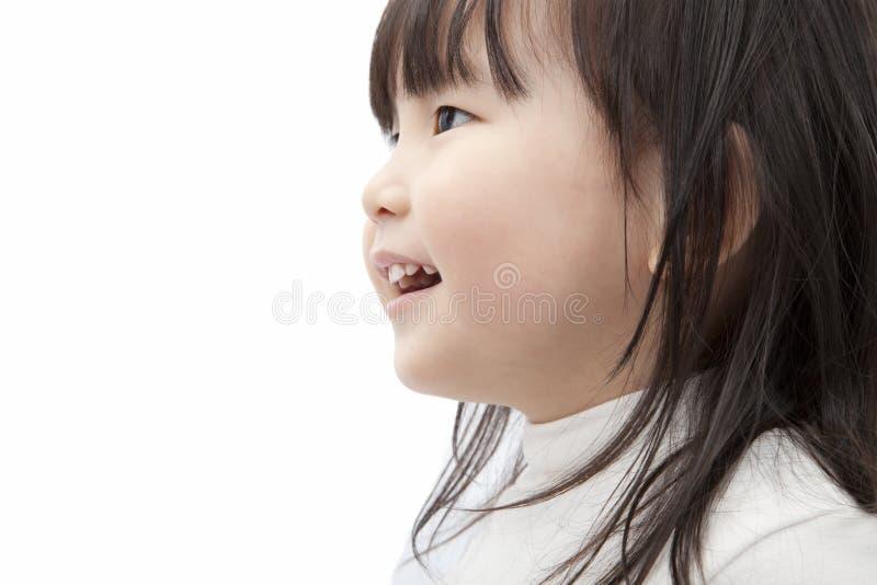 Reloj asiático y sonrisa de la niña imagenes de archivo