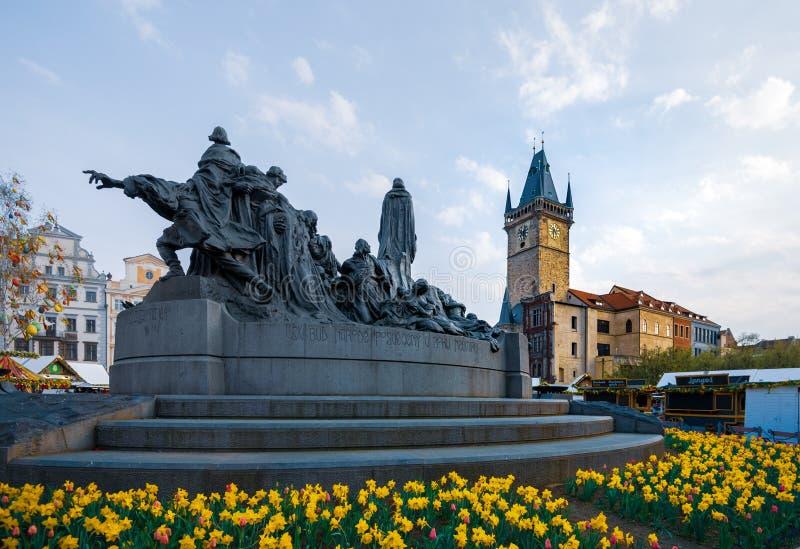 Reloj astronómico de Praga detrás de Jan Hus Monument rodeado por los narcisos en el medio de la primavera fotos de archivo