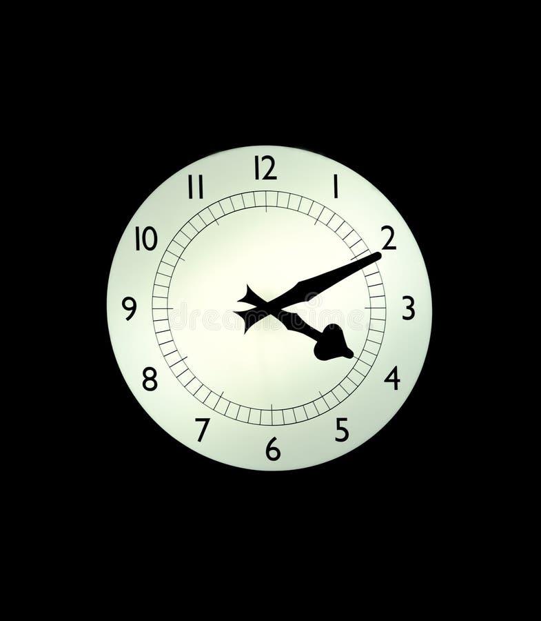 Reloj blanco retroiluminado en una pared con el fondo negro fotos de archivo libres de regalías