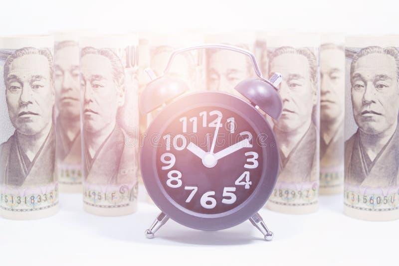 Reloj clásico en el rollo de Yen Banknote imagenes de archivo
