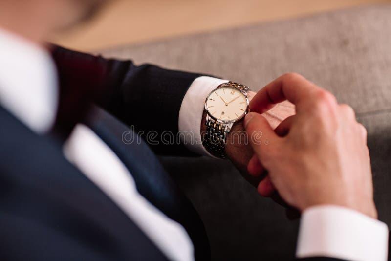 Reloj con el dial blanco en la mano de un hombre en una camisa blanca foto de archivo