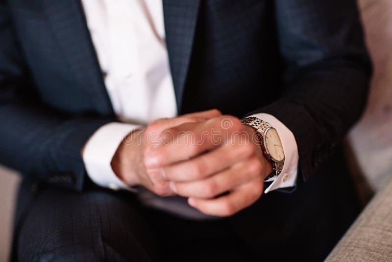 Reloj con el dial blanco en la mano de un hombre en una camisa blanca fotografía de archivo