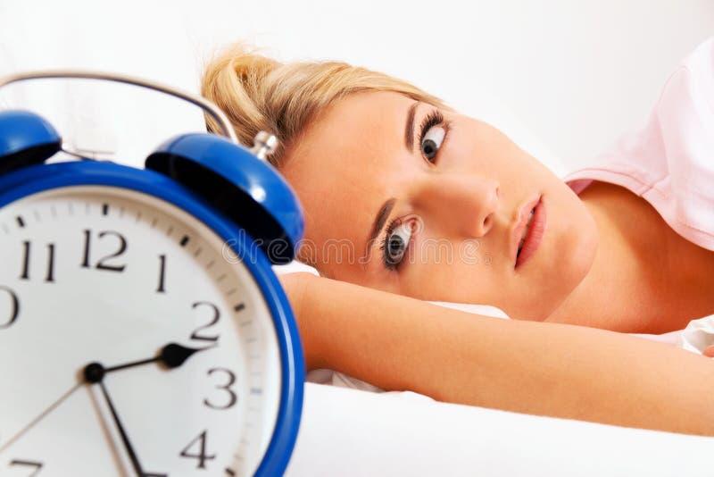 Reloj con insomne en la noche. La mujer no puede sc foto de archivo libre de regalías