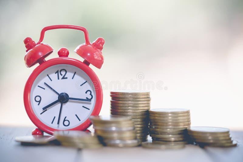 Reloj con la moneda en la tabla Inversión del tiempo o ahorro de retiro ahorre el dinero para uso futuro Conceptos del negocio y  foto de archivo