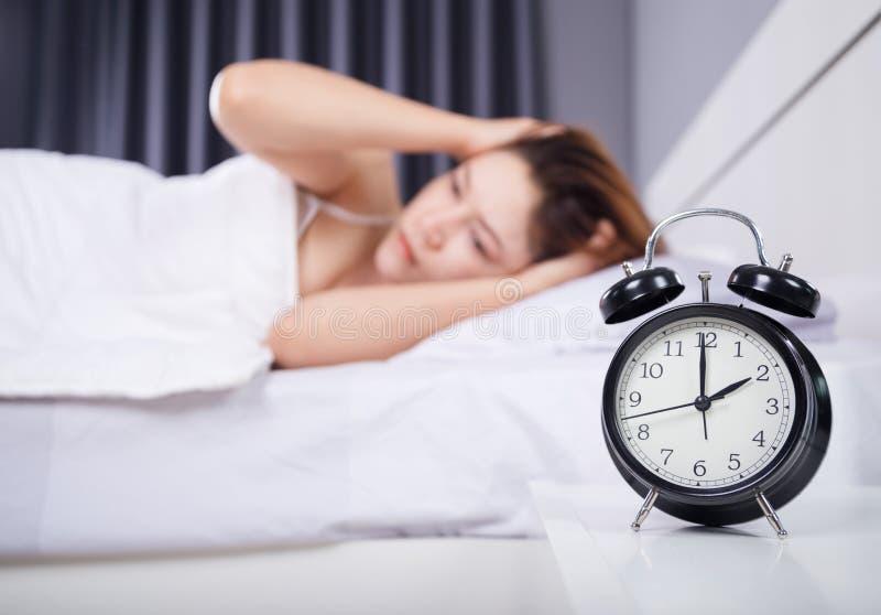 Reloj con la mujer insomne en cama imagen de archivo