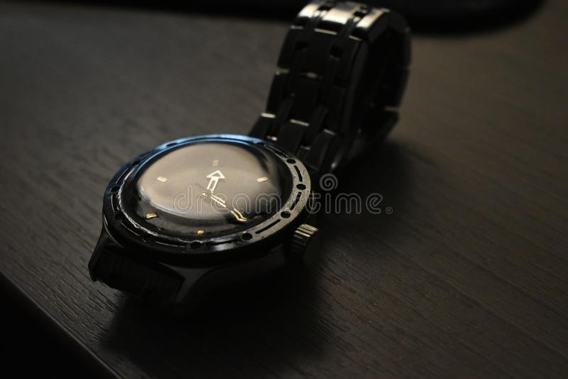 Reloj con una pulsera en la tabla fotos de archivo libres de regalías