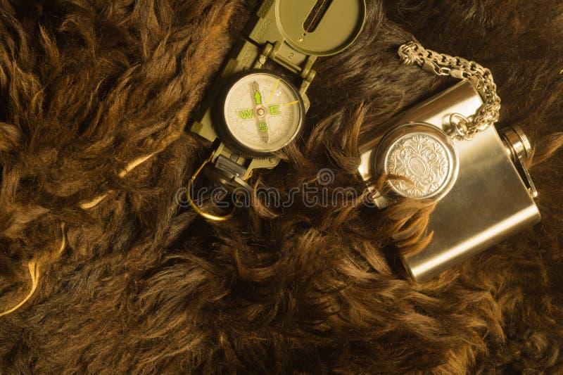 Reloj de acero viejo con el compás y el frasco en el fondo de la piel imagen de archivo libre de regalías