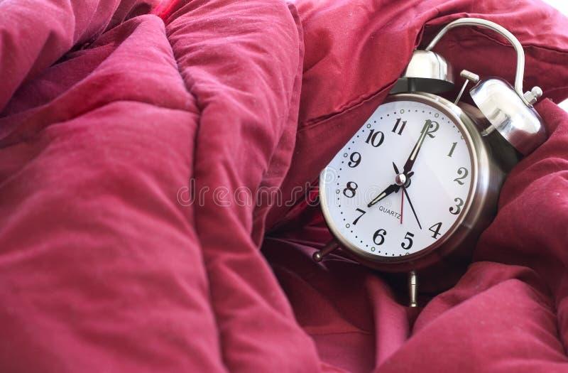 Reloj de alarma bajo la almohadilla foto de archivo libre de regalías