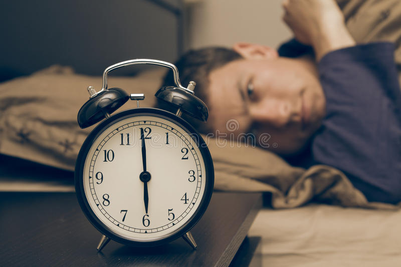 Reloj de alarma con el modelo masculino en cama en fondo. fotos de archivo libres de regalías