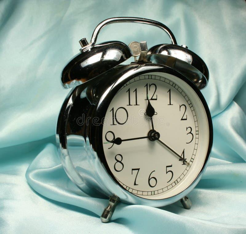 Reloj de alarma en fondo azul imagen de archivo libre de regalías