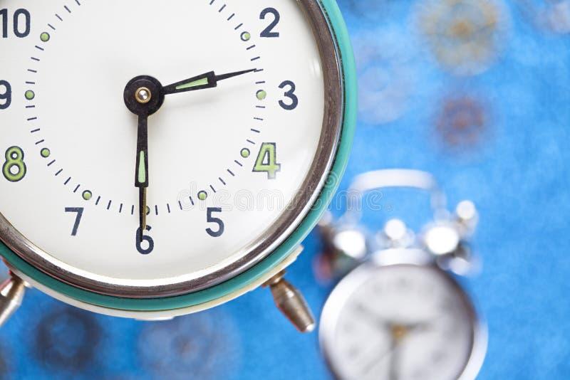 Reloj de alarma en fondo azul foto de archivo libre de regalías