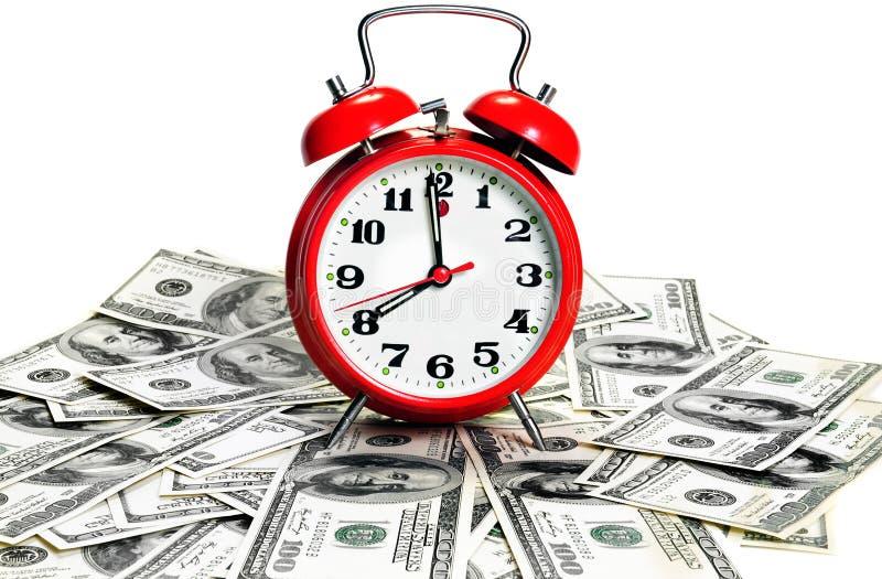 Reloj de alarma sobre dólares fotos de archivo libres de regalías