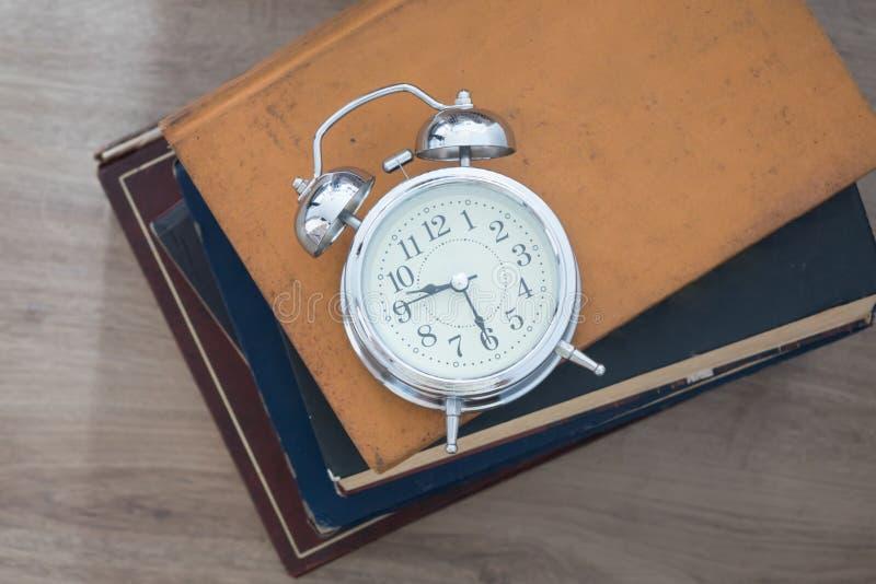 Reloj de alarma y libros imagen de archivo